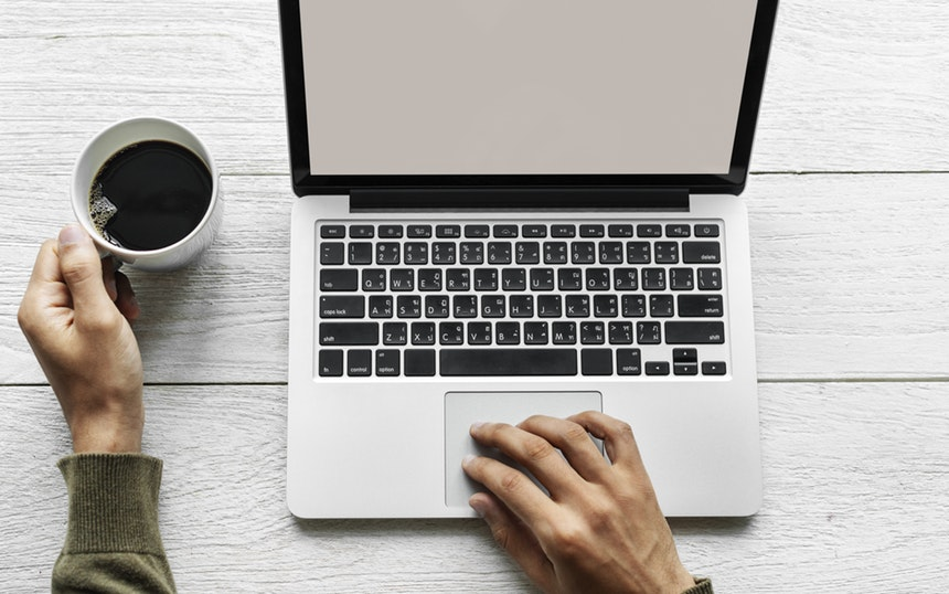 a hand on top of a laptop used to search the digital marketing trends 2019